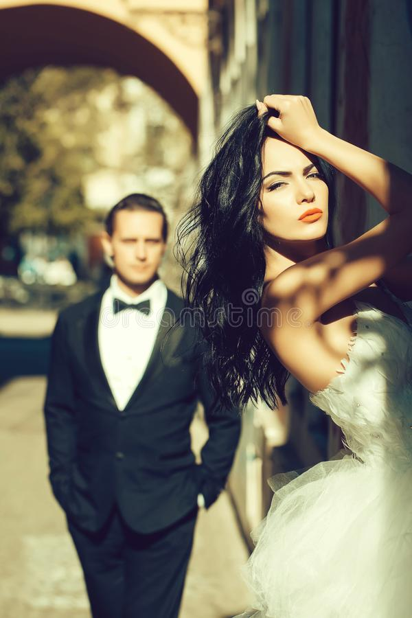 Wedding couple in arch. Young wedding couple of girl with brunette hair and red lips on pretty face in white bride dress and handsome men in black groom suit stock image
