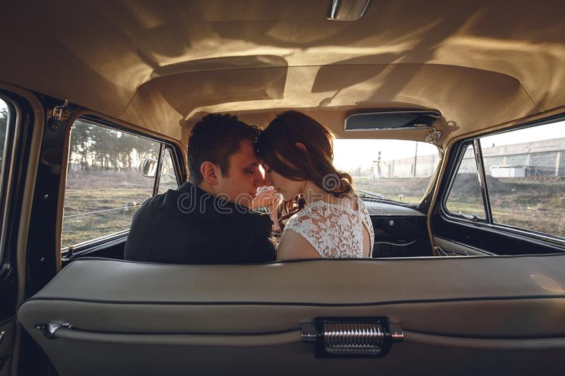 Young wedding couple sitting smiling inside retro car. just married embrace is hugging inside car. bride hugging groom who is driv stock photography