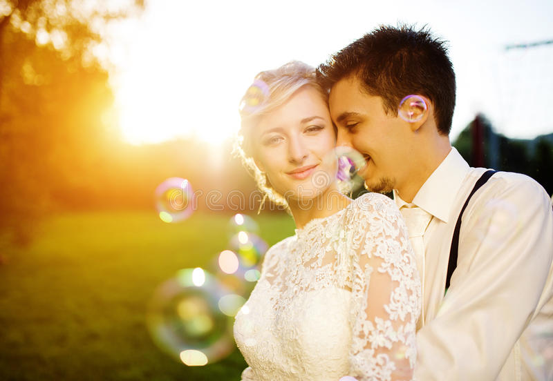 Young wedding couple on a summer meadow. Young wedding couple enjoying romantic moments outside in a summer park royalty free stock photo