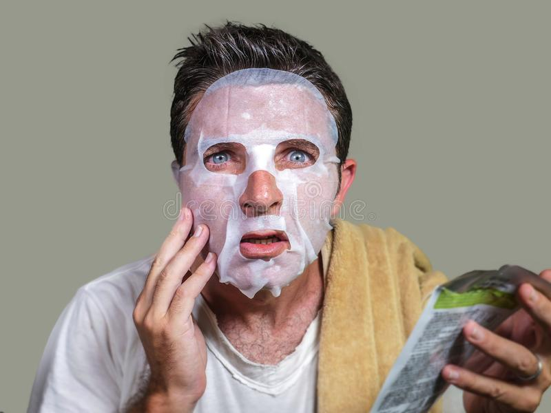 Young weird and funny man at home trying using paper facial mask cleansing applying anti aging facial treatment reading beauty royalty free stock images