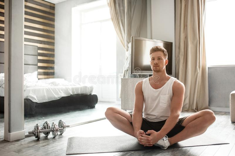 Young well-built man go in for sports in apartment. Calm peaceful guy sit in lotus pose and meditate. Stretching muscles stock photography