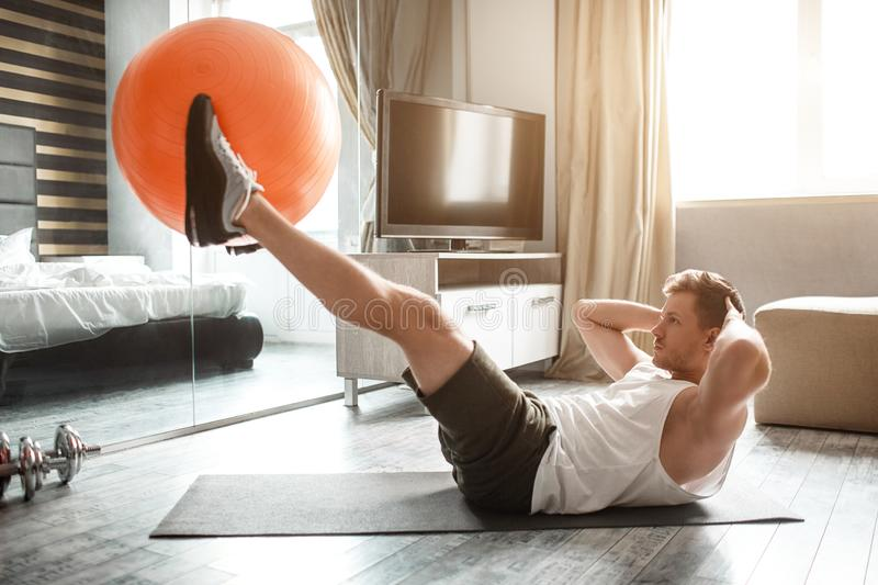 Young well-built man go in for sports in apartment. Holding big red fitness ball between feet and doing abs workout. Hands behind head royalty free stock image
