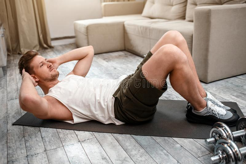 Young well-built man go in for sports in apartment. He lying on carimate and does abs. Serious and concentrated. Dumbbells on carimate royalty free stock image