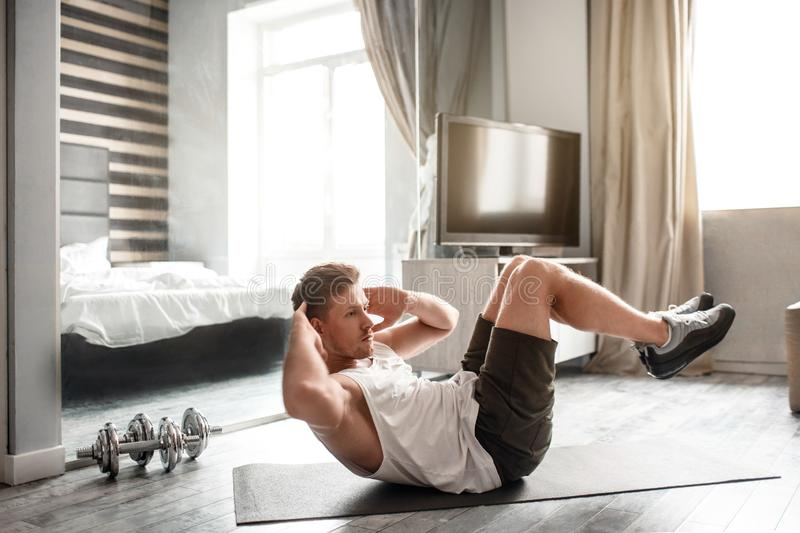 Young well-built man go in for sports in apartment. He lying on carimate and does abs workout. Guy hold hands behind. Head. Intensive workout royalty free stock photo