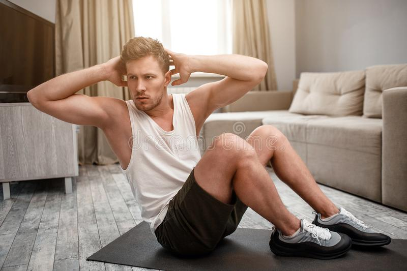 Young well-built man go in for sports in apartment. He sit on carimate and do abs. Guy hold hands behind head. Serious. And concentrated royalty free stock photography