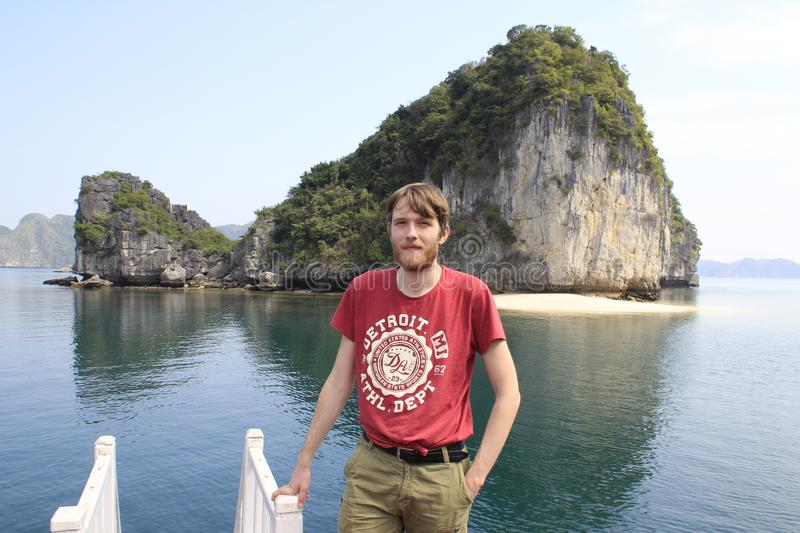Young white attractive male blond with a beard in a red t-shirt against the backdrop of a cliff and the sea in Ha Long Bay royalty free stock photography