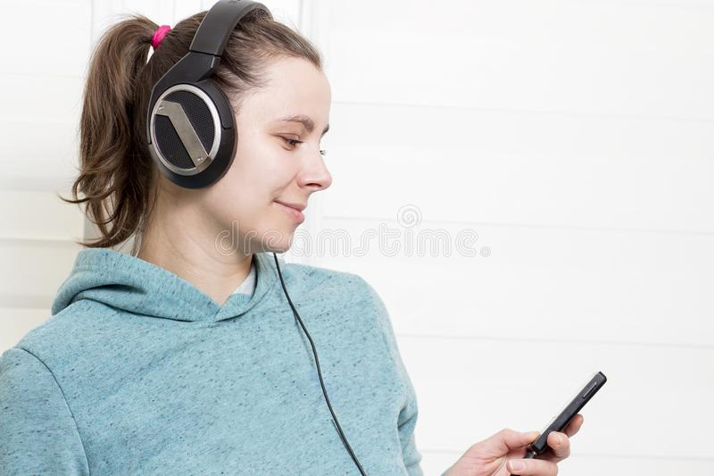 Young white brunette girl with player and in headphones listening to dance music on light house background. stock image