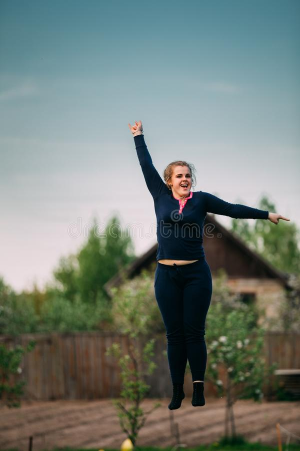 Young Caucasian Beautiful Plus Size Woman Girl Jumping On Trampoline. Young White Caucasian Beautiful Plus Size Woman Girl Jumping On Trampoline In Summer Cloudy royalty free stock photo