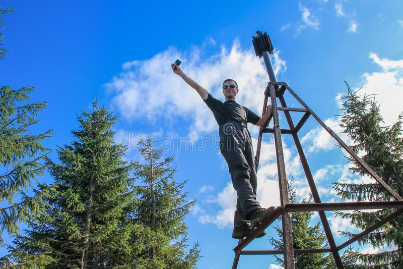 Young white Caucasian male tourist in sportswear climbed onto an iron tower in the mountains royalty free stock photography