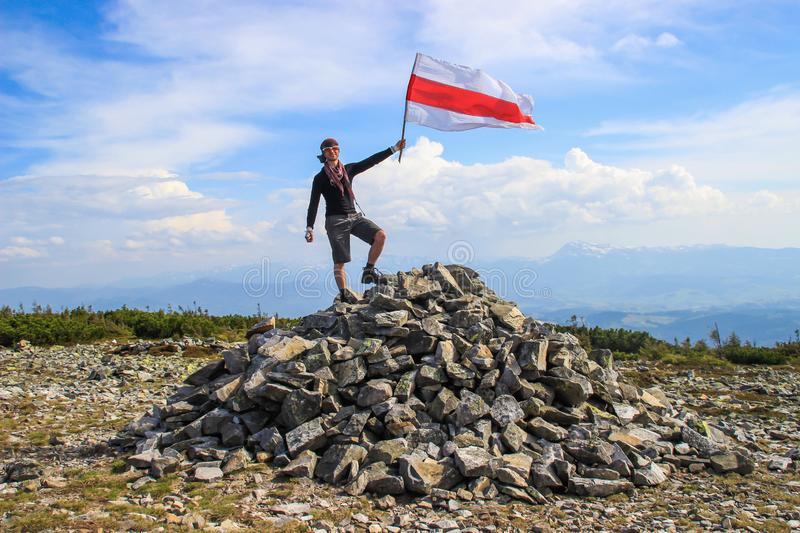 Young white Caucasian male tourist in sportswear proudly stands on a mountainous stone peak and holds a flag stock photography