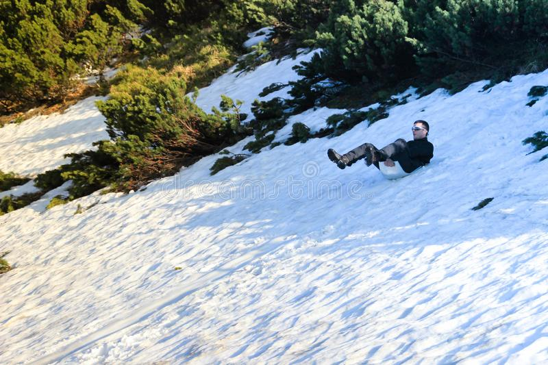 Young white Caucasian male tourist in sportswear sledding on snow in the Carpathian royalty free stock photo