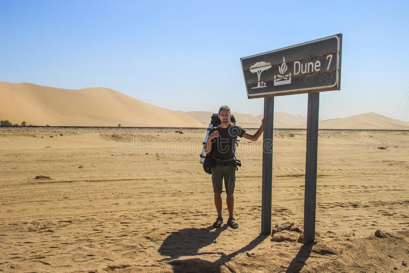 Young white Caucasian male traveler with a backpack standing next to the Dune 7 sign in the Sosusfle National Park royalty free stock image