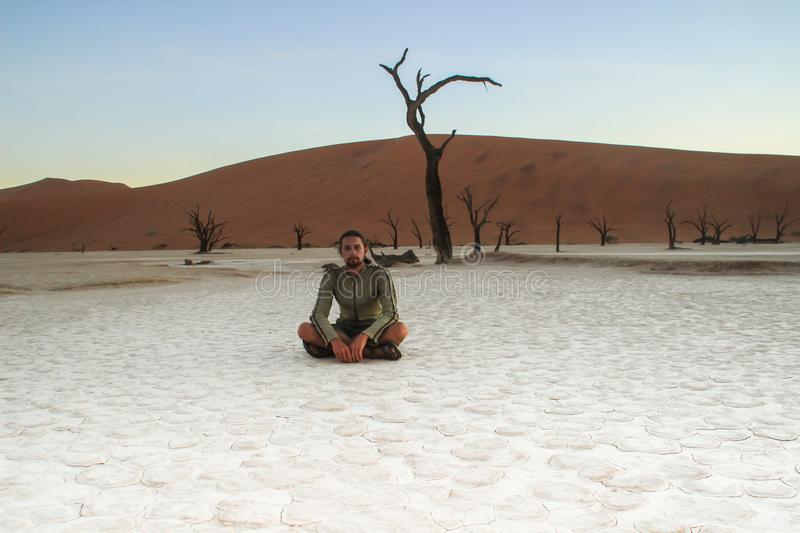 A young white Caucasian male traveler in sportswear sitting on a dry white ground in Soussefly National Park, stock image