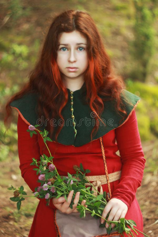 Young white Caucasian woman with big blue eyes with long red hair sits in a red medieval dress with chaperone and holds a bouquet royalty free stock photo