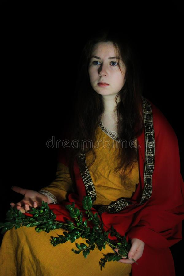Young white Caucasian woman with long red hair in the form of a Greek goddess is sitting on a black background in a yellow dress a. Nd a red raincoat with a stock image