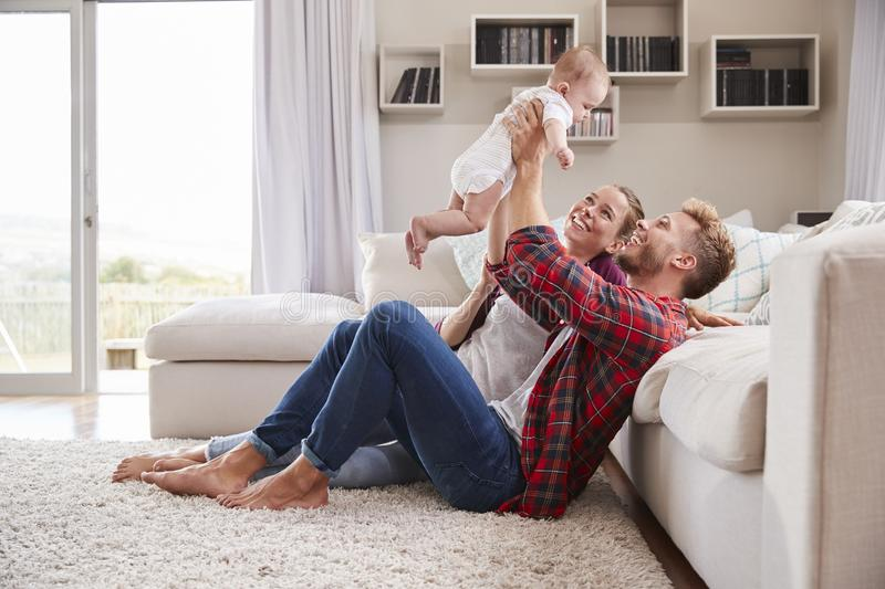 Young white couple play with their toddler in sitting room stock images