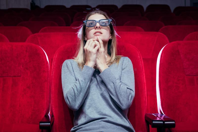 Young white europian girl, one came to the movie screening at the cinema, stock photo