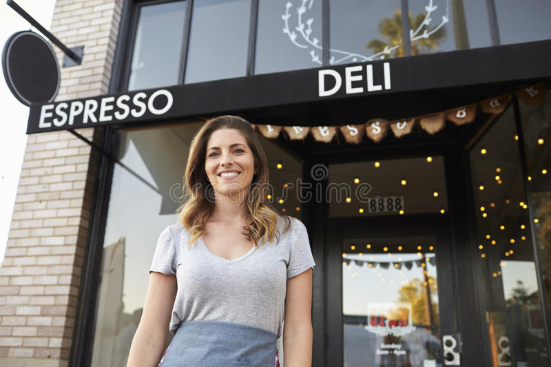 Young white female business owner standing outside cafe stock image