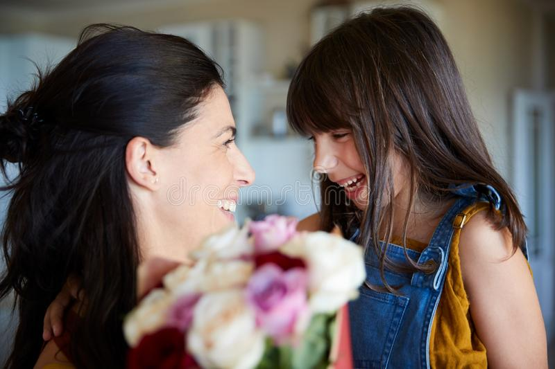 Young white girl giving her mother flowers as a gift on her birthday, close up, selective focus royalty free stock photo