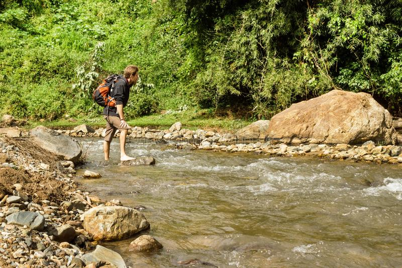 Young white man with backpack crosses the mountain river. royalty free stock images