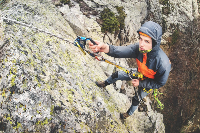 Young white man climbing a steep wall in the mountains, climbing extreme sports, wide angle Horizontal orientation stock photos