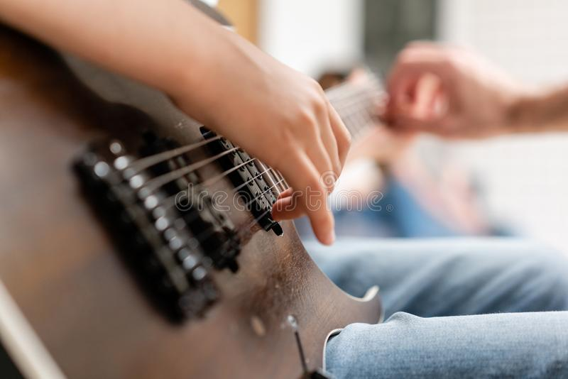 Young white man moves his hand along the strings. Concept of learning to play a musical instrument stock images