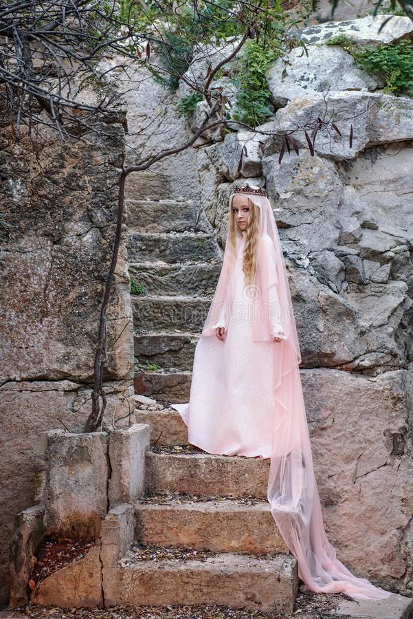 Young white pixie queen in a crown with a veil and a long dress down the stone stairs in a fabulous location royalty free stock photography