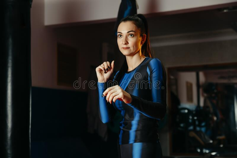Young white sports woman, put her hands in a protective gesture looking camera in the gym, ready to fight and defend herself. Conc. Ept of self-defence, sports stock images