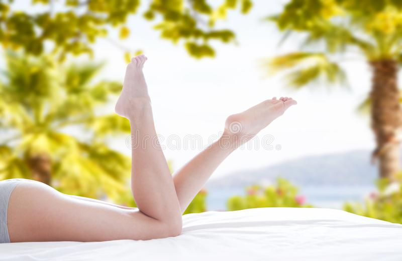 Young white woman with beautiful long legs in summer day on bed stock photo