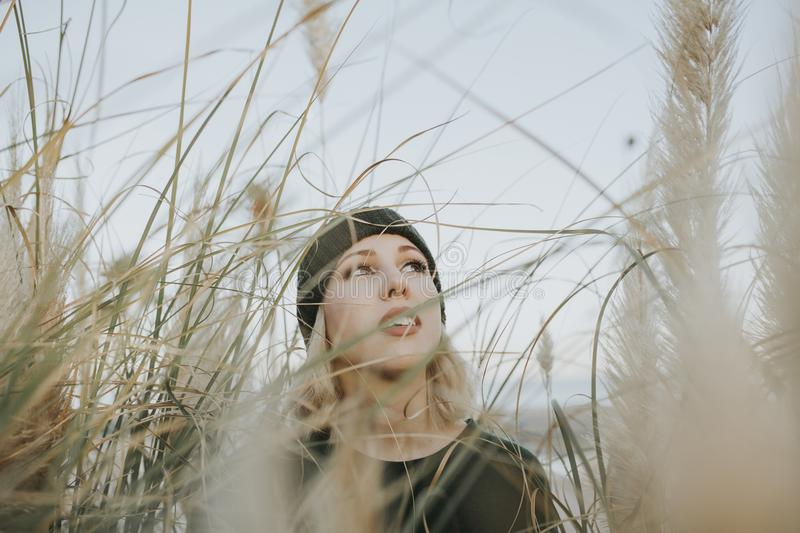 Young white woman with a knit hat on surrounded of reed plants in nature. Young white woman portrait wearing a knit hat and posing in the middle of nature stock images