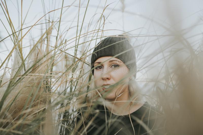 Young white woman with a knit hat on surrounded of reed plants in nature. Young white woman portrait wearing a knit hat and posing in the middle of nature royalty free stock photo