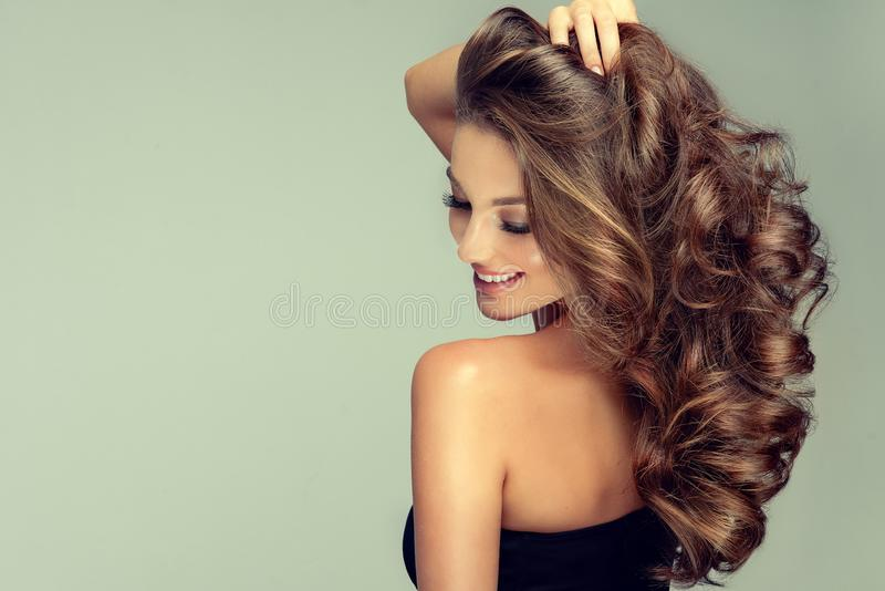 Light and sincer smile on the face of young, brown haired beautiful model with long, curly, well groomed hair. Excellent hair wav stock photography