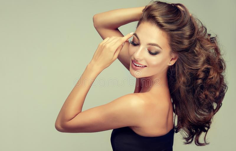 Light and tricky smile on the face of young, brown haired beautiful model with long,  curly, well groomed hair. royalty free stock images