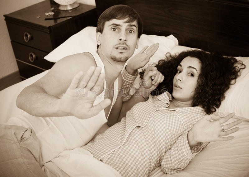 Young wife with lover caught during adultery act. Frightened young people caught at adultery in family bed stock photo