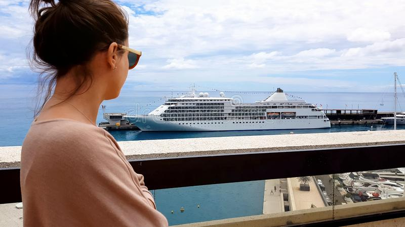 Young wife of oligarch observing liner and yachts on terrace of villa, wellness stock images