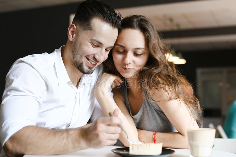 Young woman sitting with man at cafe and eating cake. royalty free stock photo