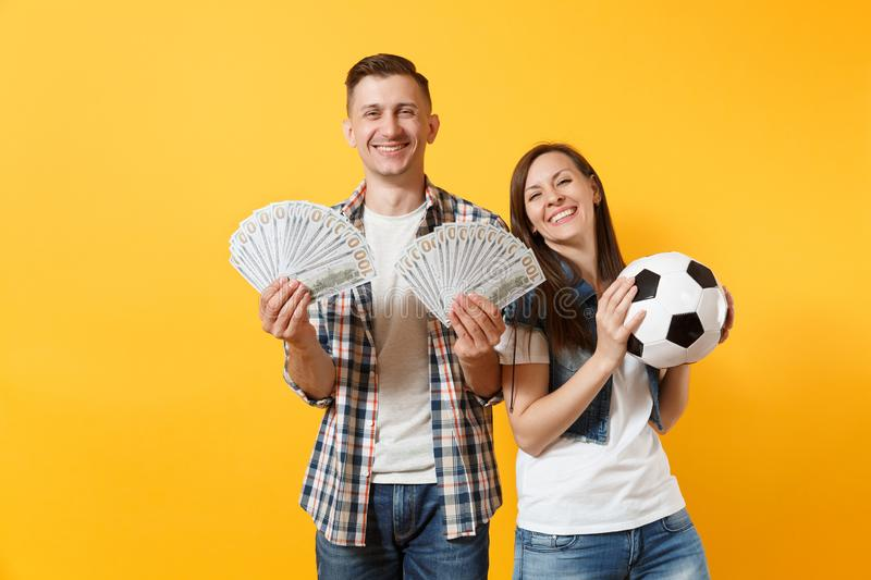 Young win couple, woman man, football fans holding bundle of dollars, cash money, soccer ball, cheer up support team stock images