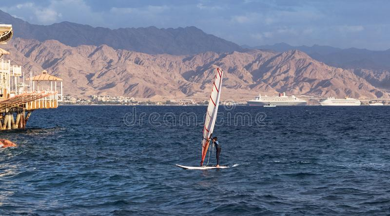 Young Windsurfer in the Gulf of Eilat Akaba. A child windsurfer sailing into the eilat marina in israel with the port of akaba jordan in the background stock photography