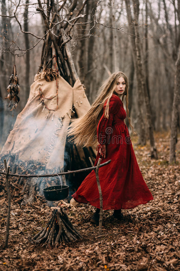 Young witch in the autumn forest royalty free stock image