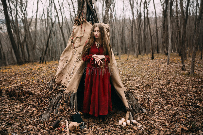 Young witch in the autumn forest stock images
