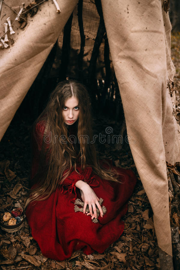 Young witch in the autumn forest royalty free stock photo