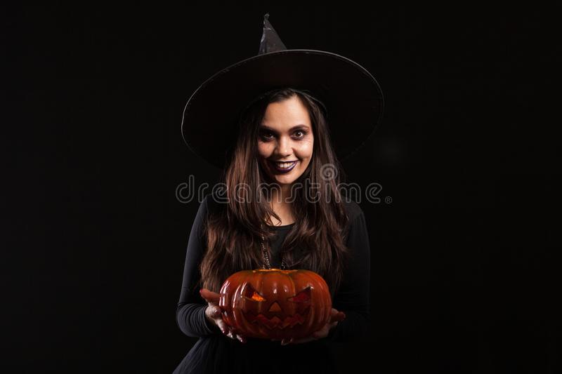 Young witch with a big hat holding a scary pumpking. Beautiful young woman in a halloween costume. Fancy costume for halloween stock images