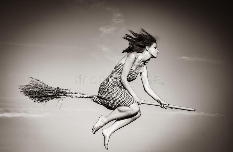 Young witch on broom flying away. Image in black and white color style stock photography