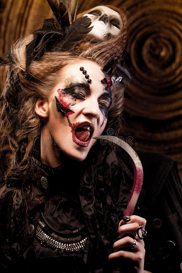 Young witch hloding sickle. Bright make up, skull, smoke- halloween theme. Studio shot royalty free stock photography