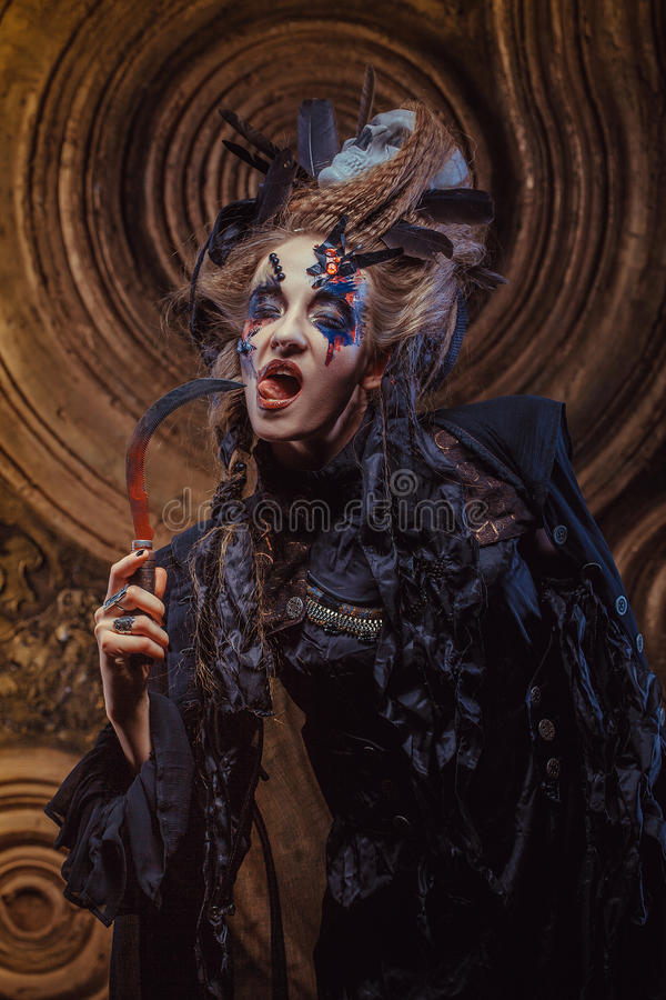 Young witch hloding sickle. Bright make up, skull, smoke- halloween theme. Studio shot stock photography