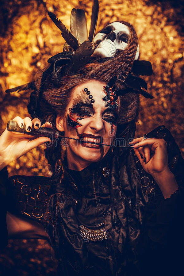 Young witch hloding sickle. Bright make up, skull, smoke- halloween theme. royalty free stock image