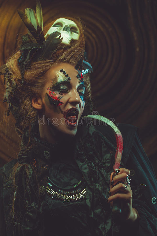 Young witch hloding sickle. Bright make up, skull, smoke- halloween theme. royalty free stock photos