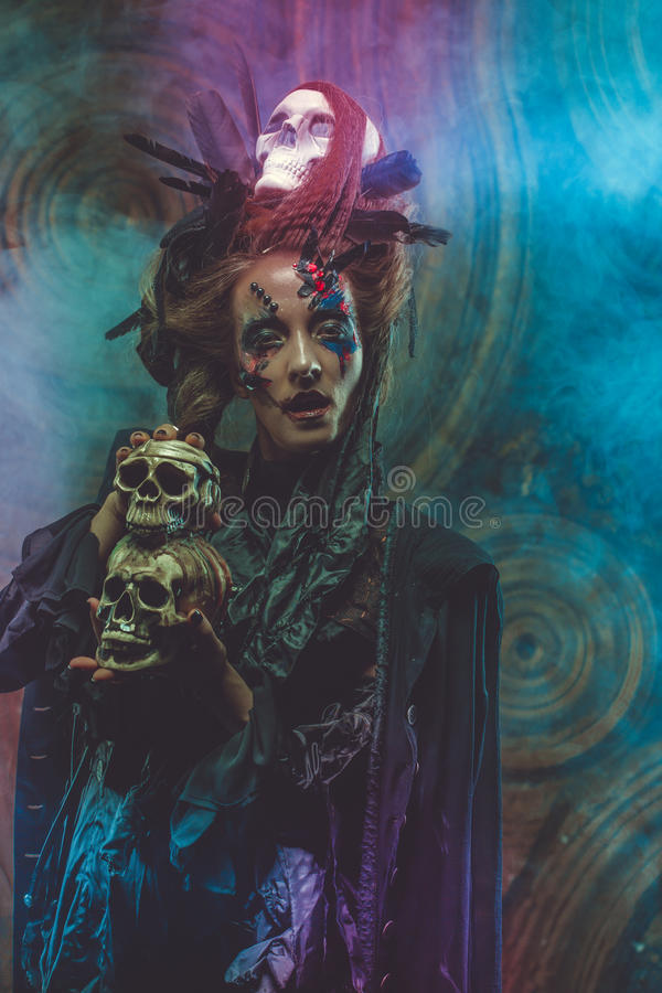 Young witch hloding skull. Bright make up and smoke- halloween theme. Studio shot stock image