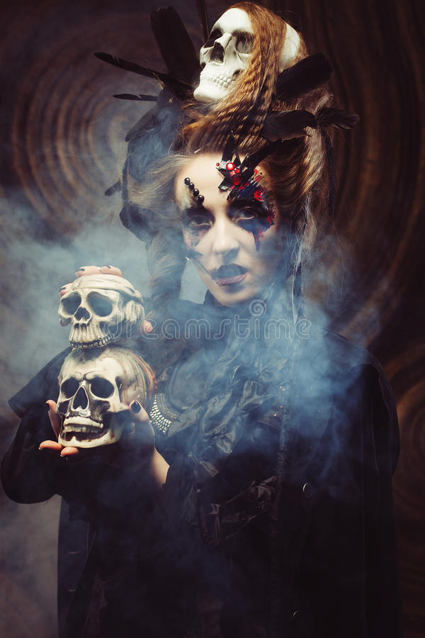 Young witch hloding skull. Bright make up and smoke- halloween theme. Studio shot royalty free stock photography