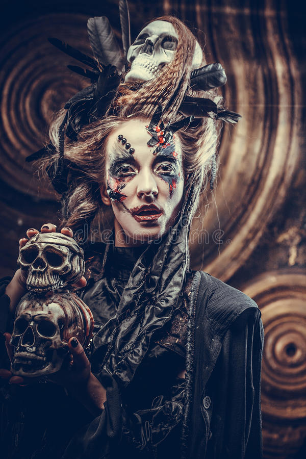 Young witch hloding skull. Bright make up and smoke- halloween theme. Studio shot royalty free stock photos